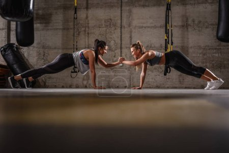Photo for Two young muscular women doing plank exercise at crossfit workout - Royalty Free Image