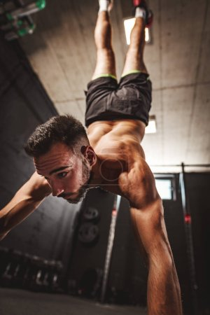 Photo for Muscular young man doing handstand exercise at cross fit workout in the garage. Rear view. - Royalty Free Image