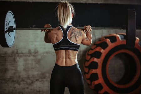 Photo for Muscular young woman doing exercise with barbell at gym - Royalty Free Image