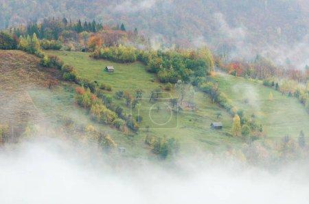 Photo pour Paysage d'automne avec maisons et arbres sur les pentes des collines. Brume matinale dans un village de montagne - image libre de droit