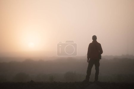 Photo for Man thinks looking at the rising sun. Morning landscape with fog - Royalty Free Image