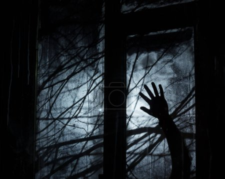 Photo pour Contexte pour la conception de fête d'Halloween. Des branches d'arbres en silhouette. Nuit noire. Main de méchant devant la fenêtre - image libre de droit