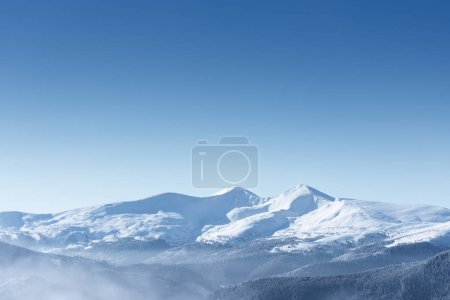 Photo for Winter background with copy space for text. Snow capped mountain peaks and clear blue sky - Royalty Free Image