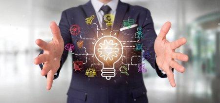 Photo pour Vue d'un homme d'affaires tenant un concept d'idée de lampe ampoule avec icône de démarrage connecté rendu 3d - image libre de droit