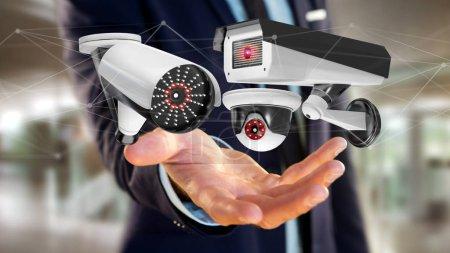 Photo pour Vue d'un homme d'affaires tenant un système de caméra de sécurité et une connexion réseau - rendu 3d - image libre de droit