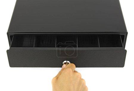 Photo pour Main avec clé essayer ouvert tiroir-caisse vide noir, vue du dessus fond blanc, concept d'audit financier ou inspection du commerce - image libre de droit