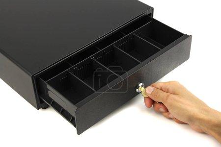 Photo pour Ouvert tiroir-caisse vide noir et main avec clé en serrure, fond blanc, concept de faillite et taxes élevées - image libre de droit