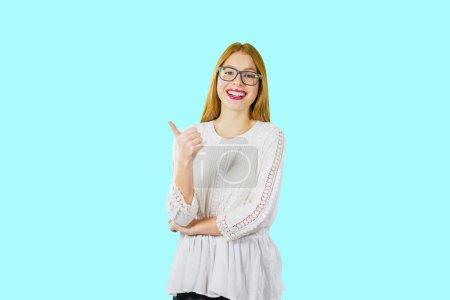 Photo pour Portrait d'une jeune belle rousse aux lunettes qui rit émotionnellement et montre la classe d'une main, photo sur un fond isolé . - image libre de droit