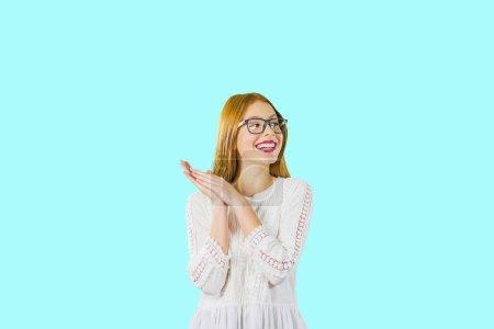 Photo pour Jeune belle fille avec de longs cheveux rouges dans des lunettes avec les paumes pliées ensemble souriant jolie regardant sur le côté, photo sur un fond isolé . - image libre de droit