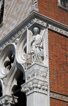 Sculpture of Archangel Raphael with Tobias, detail of the Doge Palace, St. Mark Square, Venice, Italy, UNESCO World Heritage Site