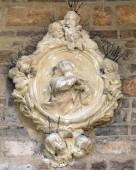 Virgin Mary relief on facade of church in Verona, Italy