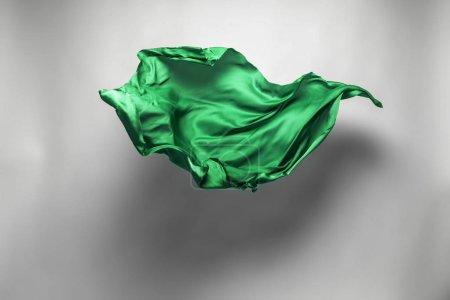 Photo pour Morceau abstrait de tissu vert volant, prise de vue studio à grande vitesse - image libre de droit