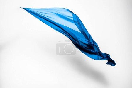 Photo pour Morceau abstrait de tissu bleu volant, prise de vue studio à grande vitesse - image libre de droit