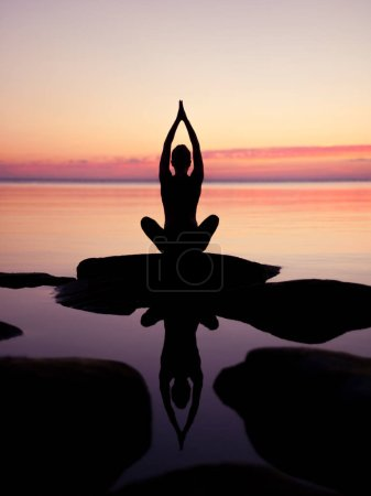 Photo for Caucasian fitness woman practicing yoga on the beach at sunset - Royalty Free Image