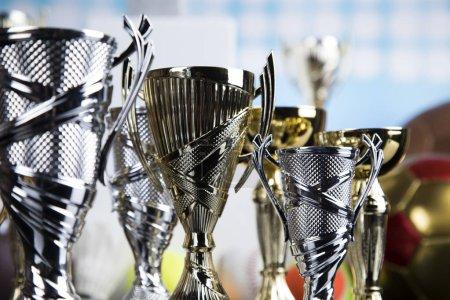 Photo pour Tasses de prix gagnants sur podium blanc, fond sport - image libre de droit