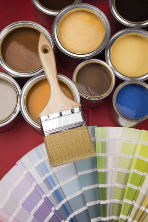 Photo for Buckets full of rainbow colored oil paint, red background - Royalty Free Image
