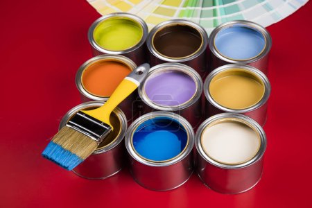 Photo for Open buckets with a paint and brush, red background - Royalty Free Image