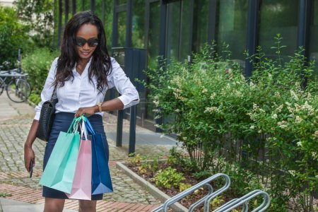 Photo pour African bussineswoman se tient dehors et regarde sa montre - image libre de droit