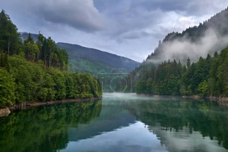beautiful landscape with lake and misty forest in mountains in a rainy day