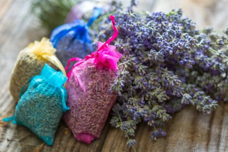 Closeup of a bouquet of lavender and bags on a wooden board