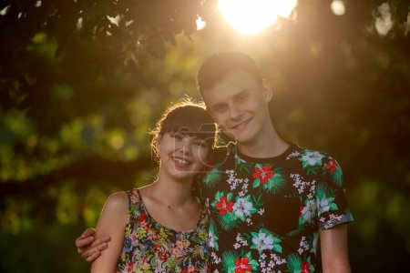 Happy young couple under a big tree at sunset