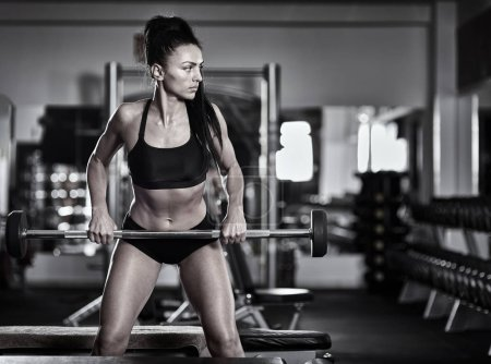 Photo for Athletic woman doing barbell rows in the gym - Royalty Free Image