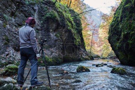 professioneller Naturfotograf mit Kamera auf Stativ in einer Schlucht