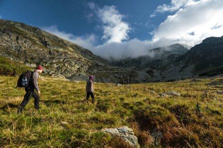 Photo pour Un couple de randonneurs randonnée sur un sentier dans la montagne - image libre de droit
