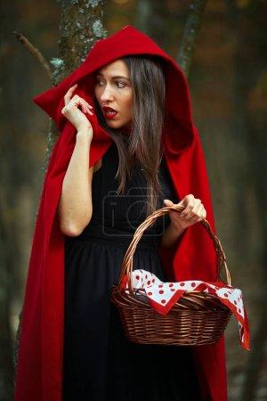 Photo pour Portrait rapproché d'une femme cosplay capuche rouge dans la forêt - image libre de droit