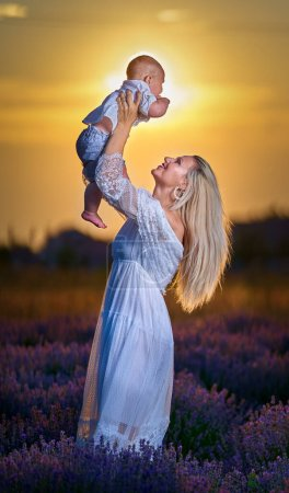 Photo for Young mother playing with her son in a lavender field at sunset - Royalty Free Image