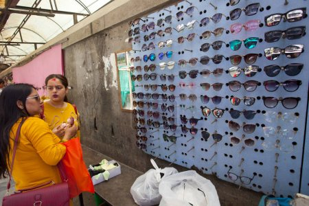 KATHMANDU, NEPAL - JULY 17, 2018: Unidentified Nepal women buying sunglasses in local market in the Thamel district, Kathmandu. Thamel is a tourist district with many hotels, souvenir shops