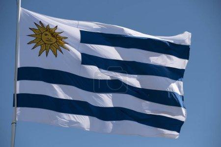 Photo pour Drapeau uruguayen agitant dans le vent sur fond bleu ciel. Drapeau de pays Uruguay avec emblème national . - image libre de droit
