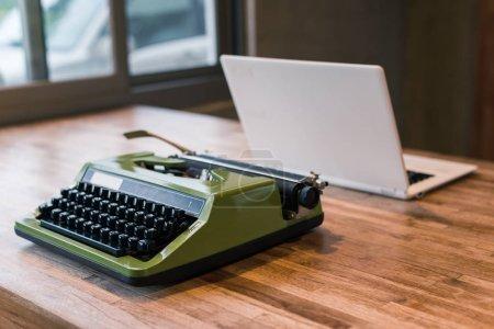 Photo pour Vieille machine à écrire et l'ordinateur portable sur la table - image libre de droit