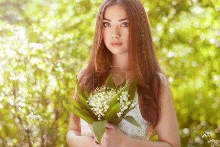 Photo pour Portrait de belle jeune femme avec lys de la vallée. Fille sur la nature. Fleurs printanières. Beauté de mode - image libre de droit