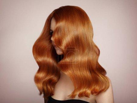 Photo pour Fille rousse aux cheveux bouclés longs saine et brillante. Soins et beauté. Beau modèle femme avec une coiffure ondulée. Maquillage et robe noire - image libre de droit
