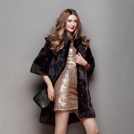 Photo pour Mode Portrait Jeune femme en fourrure noire Manteau. Fille avec coiffure élégante posant sur un fond gris. Lady Posing in Eco-Fur Coat. Belle femme d'hiver de luxe. Modèle de mode en robe dorée - image libre de droit