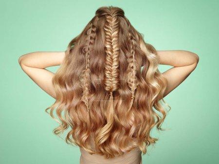 Foto de Chica rubia con pelo rizado largo y brillante. Hermosa modelo mujer con peinado rizado. Cuidado y belleza del cabello. Señora con el pelo trenzado - Imagen libre de derechos