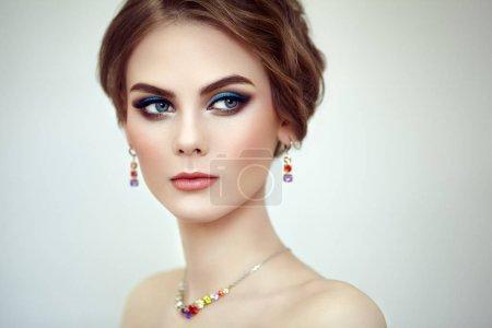 Photo pour Verticale belle femme avec des bijoux. Maquillage de mode et cosmétiques. Coiffure élégante. Flèches bleues de maquillage. Beauté et accessoires - image libre de droit