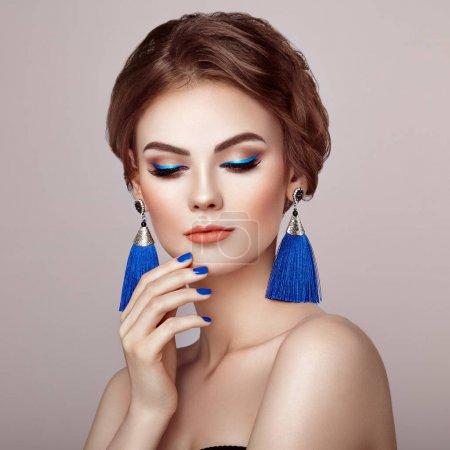 Photo pour Belle femme avec de grandes boucles d'oreilles glands bijoux couleur bleue. Maquillage parfait et coiffure élégante. Flèches de maquillage bleues. Manucure ongles bleus - image libre de droit