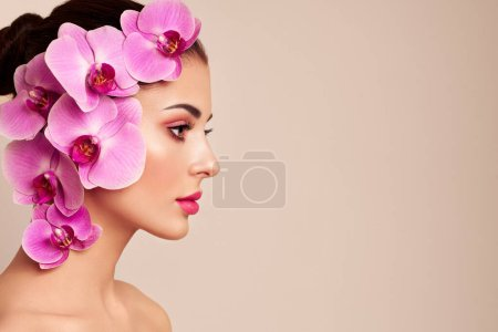 Photo for Portrait of beautiful young woman with orchid. Brunette woman with luxury makeup. Perfect skin. Eyelashes. Cosmetic eyeshadow. Purple flowers - Royalty Free Image