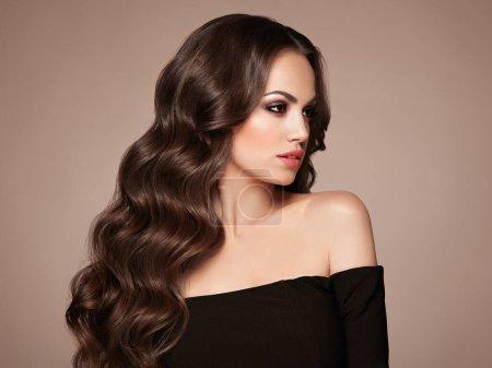 Photo pour Brunette fille avec de longs cheveux bouclés sains et brillants. Soins et Beauté. Belle femme modèle avec coiffure ondulée. Maquillage et robe noire - image libre de droit