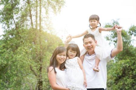 Foto de Los padres y los niños mirando a cámara en el parque. Familia asiática retrato al aire libre. - Imagen libre de derechos