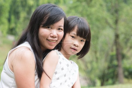 Photo for Asian family outdoors portrait. Mother and daughter bonding at garden park. - Royalty Free Image