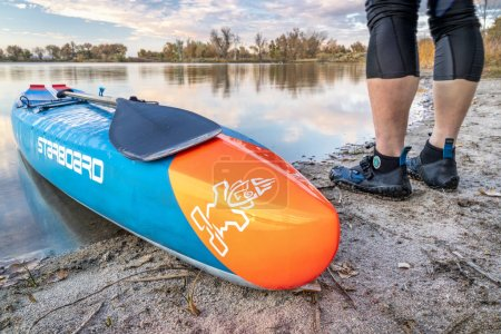 Photo pour Fort Collins, Colorado, Usa - 17 octobre 2018: Course debout paddleboard sur un lac calme dans un paysage d'automne de northern Colorado - 2018 modèle de toutes les étoiles Sup par tribord. - image libre de droit