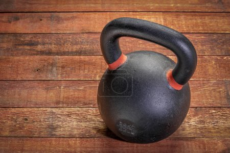 Photo for Heavy iron kettlebell on a rustic wood background with a copy space, fitness concept - Royalty Free Image