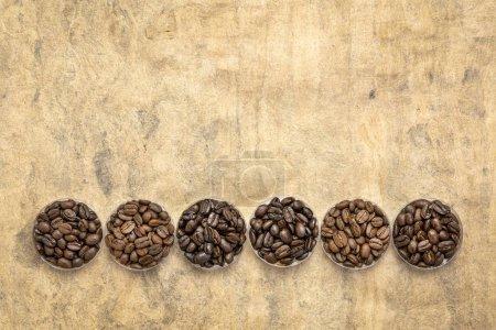 Foto de Muestreo de granos de café de diferentes partes del mundo - vista aérea de tazones de fuente redondos contra hechos a mano con textura papel con un espacio de copia - Imagen libre de derechos