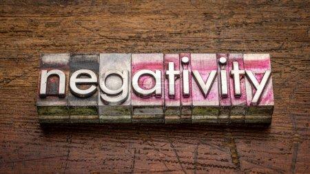 Negativitätswort abstrakt in kiesigem Vintage-Buchdruckmetall gegen rustikales, verwittertes Holz, Arbeit, Stress, Mentalität und Lifestylekonzept