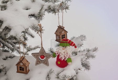 Snow-covered  spruce with a retro Christmas toy. M...