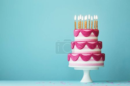 Photo for Pink tiered birthday cake with birthday candles - Royalty Free Image