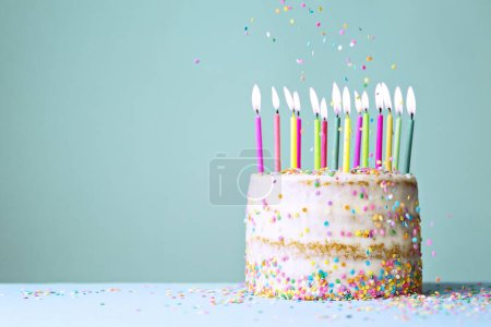 Photo for Naked funfetti birthday cake with colorful candles and falling sprinkles - Royalty Free Image
